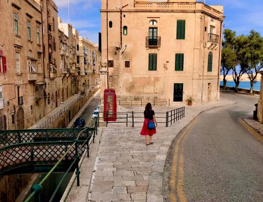 Girl walks past red telephone box near the Grand Harbour in Valletta