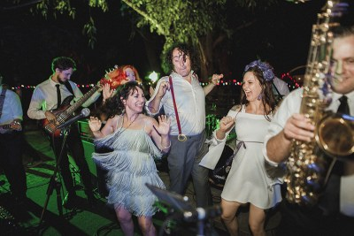 A retro music festival-style tent village wedding with four dresses & a eye-popping headpiece