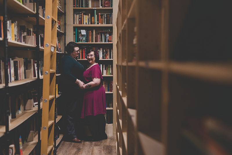 Love in the stacks: a literary engagement shoot with two cute brides-to-be