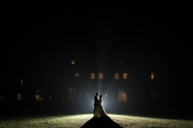 A bride and groos at night in front of a mansion