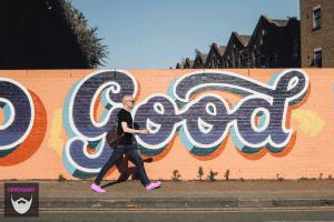"""Bildnachweis: Bald man wearing pink shirt and sunglasses walks on sidewalk in front of graffiti that reads """"good"""" by Volkan Olmez Unsplash.com License, bearbeitet von Lukas Klette."""