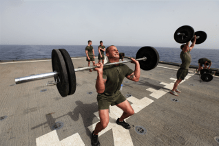 Staff Sgt. Jeffrey Perry, a Middlesex, N.J., native and the motor transportation chief with Motor Transportation Platoon, Combat Logistics Battalion 24, 24th Marine Expeditionary Unit, lifts weights during a CrossFit workout on the flight deck of the USS Gunston Hall, June 14, 2012. The 24th MEU, along with the Iwo Jima Amphibious Ready Group, is currently deployed to the U.S Central Command area of operations as a theater reserve and crisis response force. The group is providing support for maritime security operations and theater security cooperation efforts in the U.S. Navy's 5th Fleet area of responsibility. (Photo by Sgt. Richard Blumenstein)