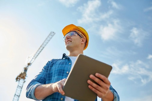 builder in hardhat with tablet pc at construction