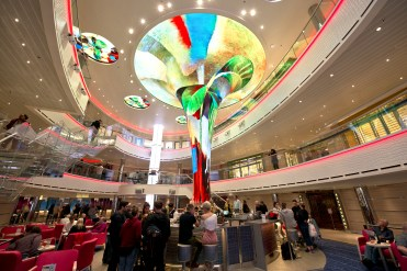 Guests aboard Carnival Horizon occupy the cruise liner's main atrium highlighted by the Dreamscapes LED sculpture. Photo by Andy Newman/Carnival Cruise Line