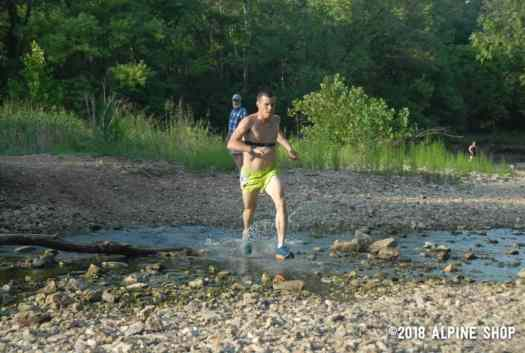 Benjamin Hudson crosses a creek in Trail Run