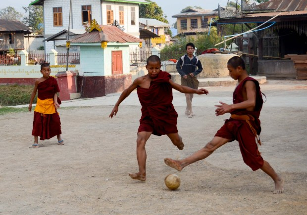 Young monks play soccer outside of the monastery during a break from study. Flamboyant goal celebrations are universal.