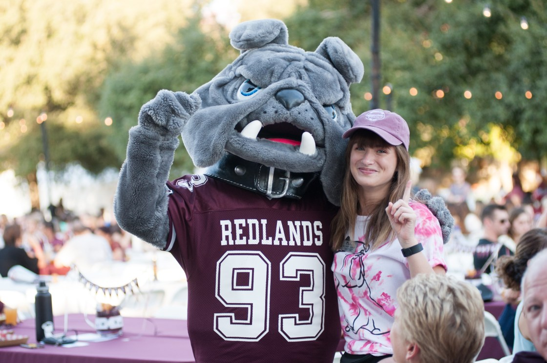 A University of Redlands student with Bulldog mascot.