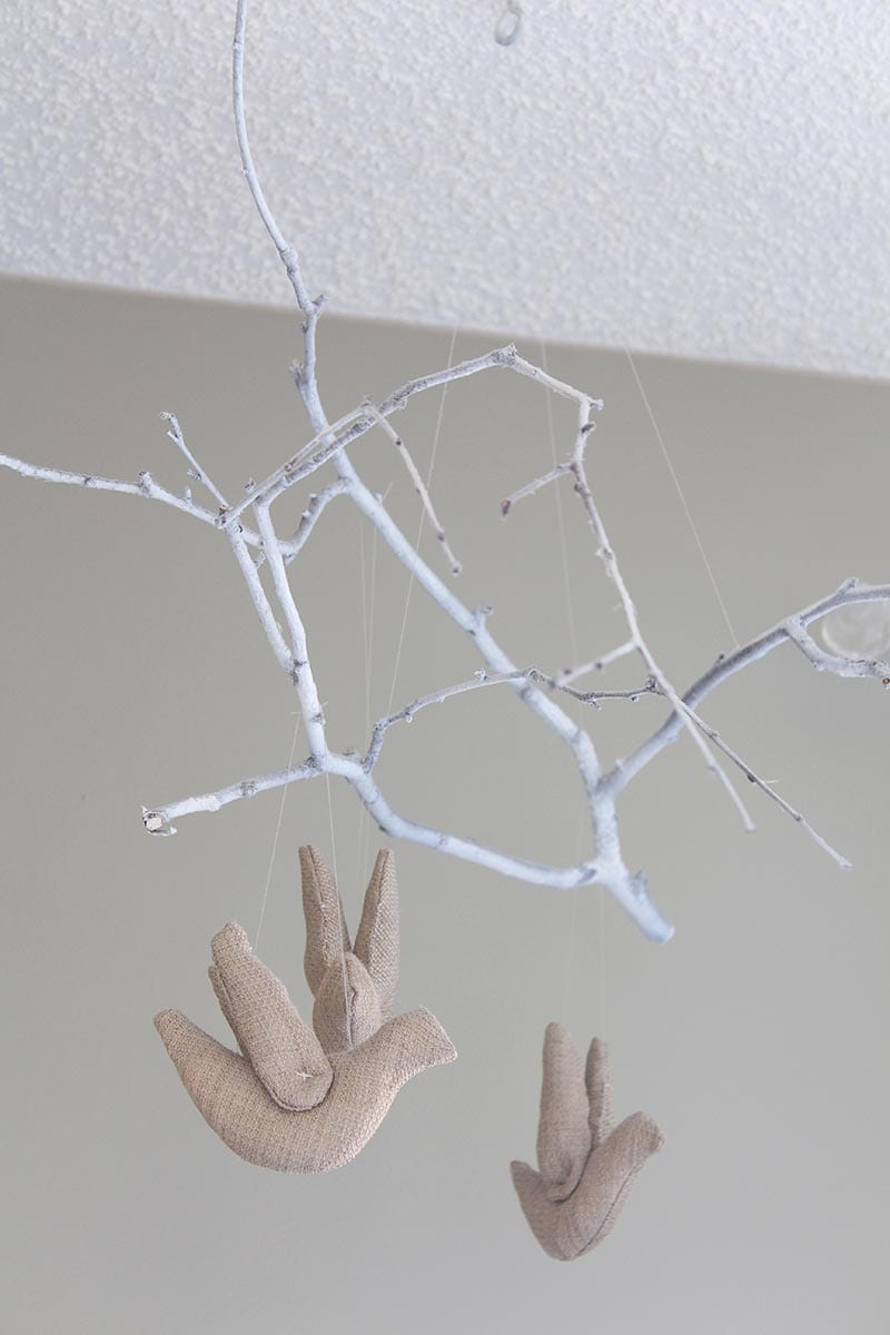 DIY white tree branch mobile with beige birds.