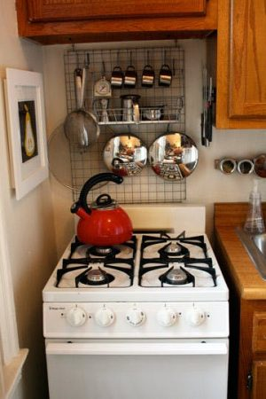 Install a wire mesh board behind your stove to store your kitchen essentials and save a ton of space.