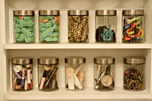 Use glass canisters to neatly organize your makeup and other beauty supplies.