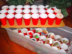 Glue plastic cups to cardboard and use it as a quick and cheap way to store your Christmas ornaments