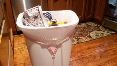 Attach command hooks to the outside of your trash can to prevent the bag from falling inside of it.