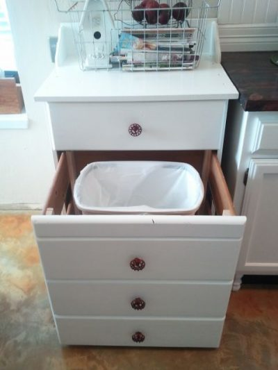 Turn an old, unused dresser into a storage place for your trash can.