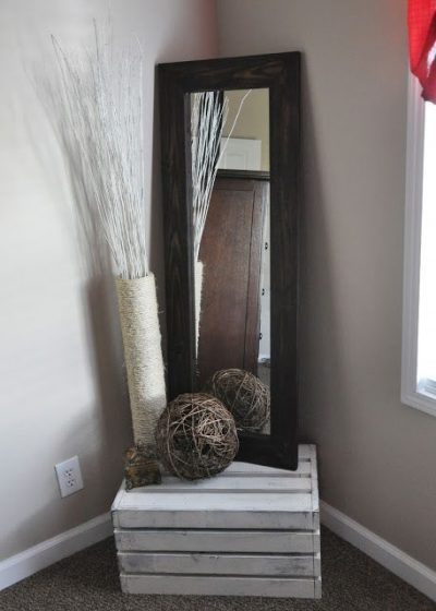 Use a wooden pallet to prop a large mirror and other decorations.