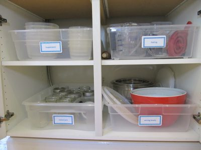 Keep your kitchen cabinets super organized by using plastic bins to organize kitchen supplies.