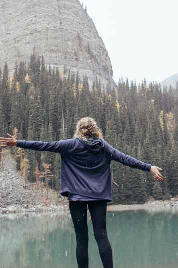 woman with arms outstretched standing on coast of lake