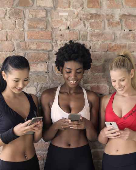 three woman in assorted color sport bras holding and watching their smartphones