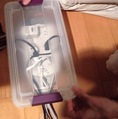 Keep crawling hands and feet away from dangerous plugins and power cords by cutting a hole in a plastic bin. Thread the wires through, pop the lid on, and voila! They're out of reach. | Toddler Parenting Hacks