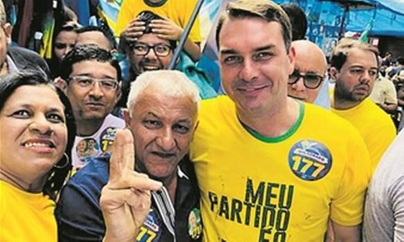 Em 2018, Flávio e o deputado federal Lourival Gomes, com Queiroz ao fundo Foto: Reprodução