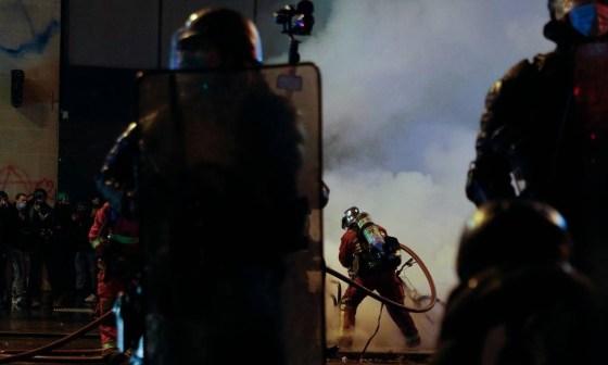 Bombeiro apaga fogo durante manifestação contra violência policial em Paris Foto: GEOFFROY VAN DER HASSELT / AFP