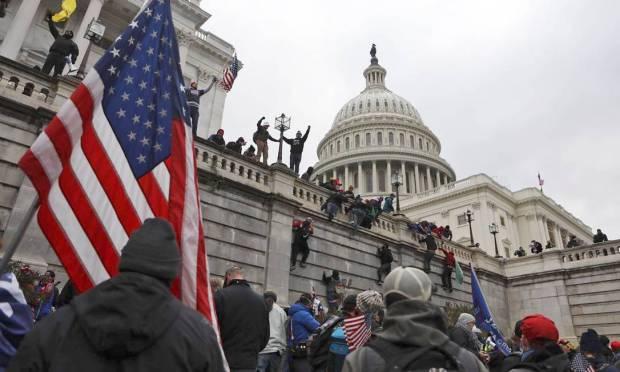 Donald Trump supporters climb the walls of the US Capitol in Washington Photo: JIM URQUHART / REUTERS