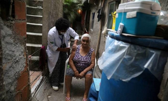Maria do Socorro Correia, 78, receives a coronavirus vaccine at her home in the Rocinha favela in Rio de Janeiro Photo: PILAR OLIVARES / REUTERS