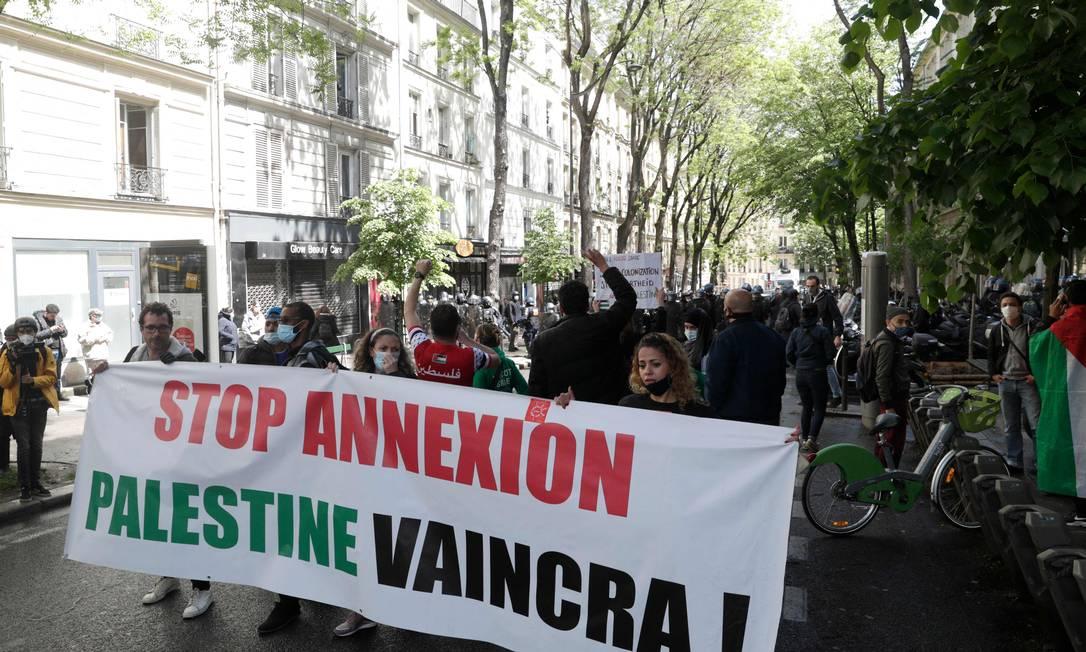 Manifestantes seguram uma faixa que diz 'pare a anexação - a Palestina vai vencer' durante uma manifestação em solidariedade aos palestinos, em Paris, França Foto: GEOFFROY VAN DER HASSELT / AFP - 15/05/2021