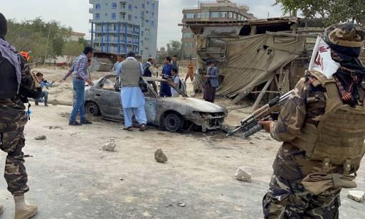 Sob o olhar de tropas do Talibã, moradores se aproximam de veículo atingido por míssel em Cabul, no Afeganistão Foto: STRINGER / REUTERS