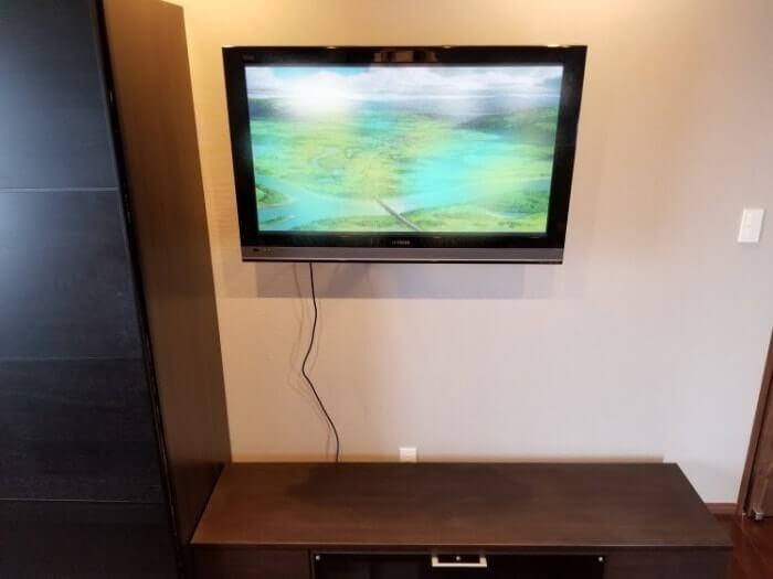 寝室 壁掛けテレビ ケーブルがぶら下がっている