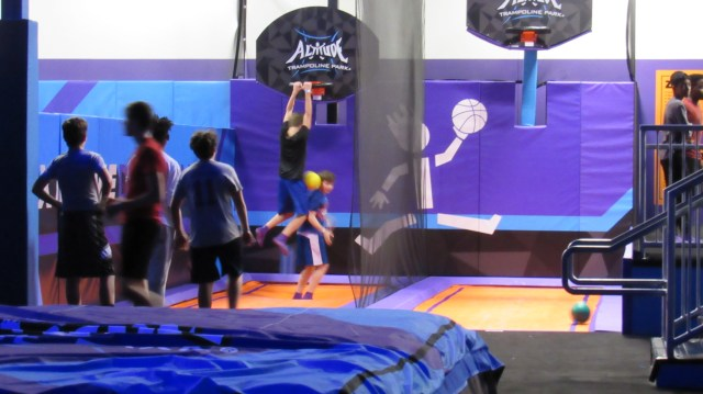 "Swoosh! A jumper practicing his basketball skills in Altitude's ""Trampoline Basketball"" area."