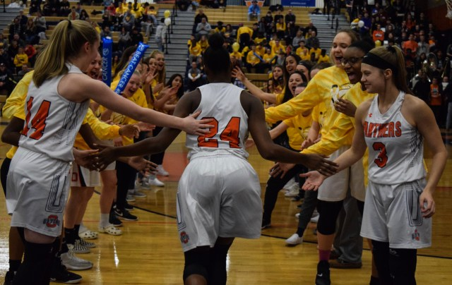 Three OHS girls basketball athletes (14, 24, and 3) high-five as they come out on the court.