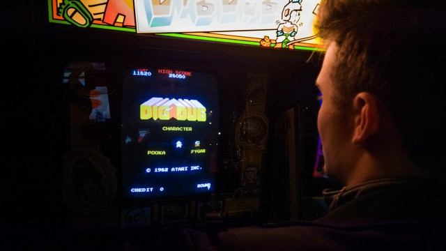 Guy in arcade playing Dig Dug
