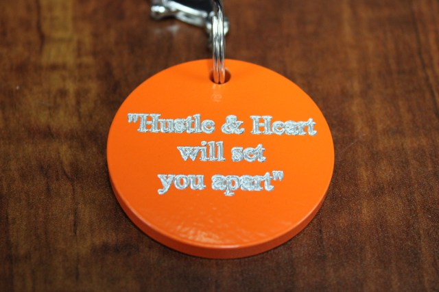 "Orange keychain saying ""Hustle and heart will set you apart"""
