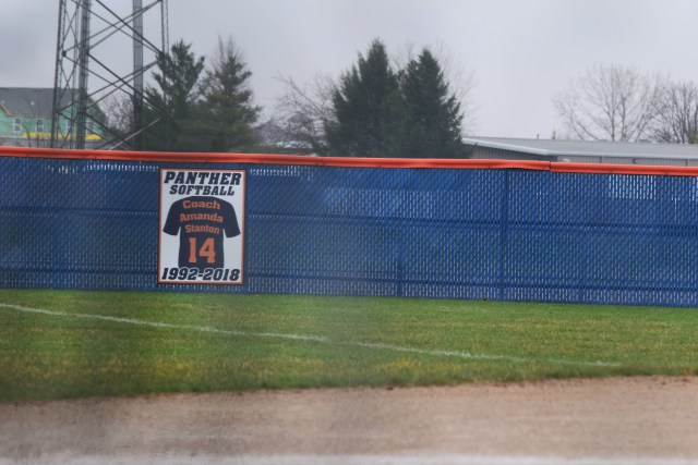 """The sign posted in the outfield. Text: """"Coach Amanda Stanton, 14, 1992-2018"""""""