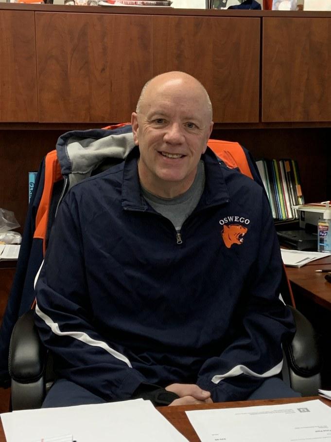 Darren Howard in his office wearing an Oswego High School zip-up.