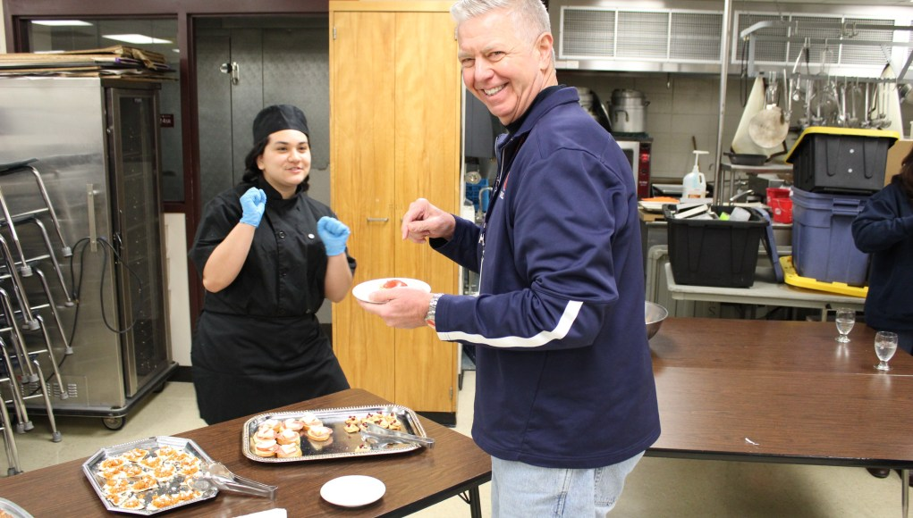 OHS Principal Mike Wayne samples a dish with a big smile across his face.