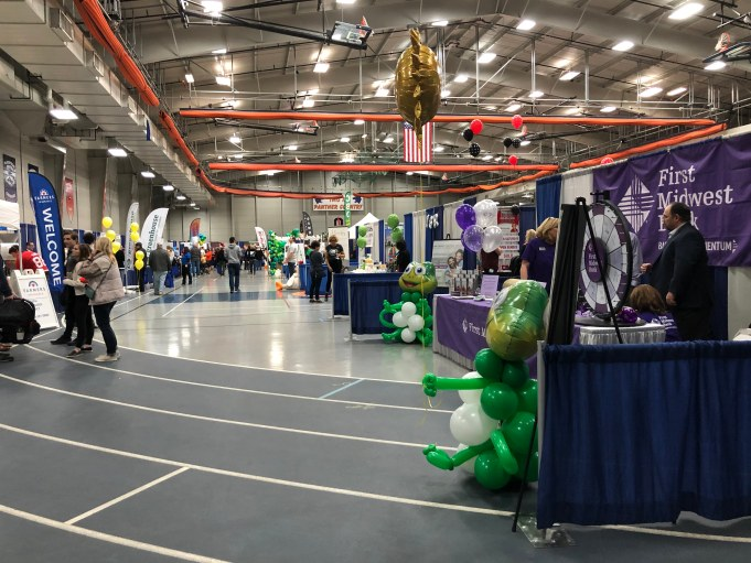 The Oswego High School fieldhouse full of tables of different businesses for people to apply for jobs.
