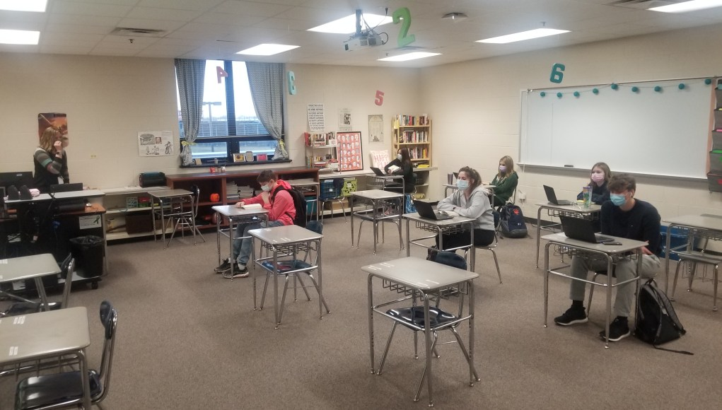 students are wearing masks in their classroom and are doing work on their computers