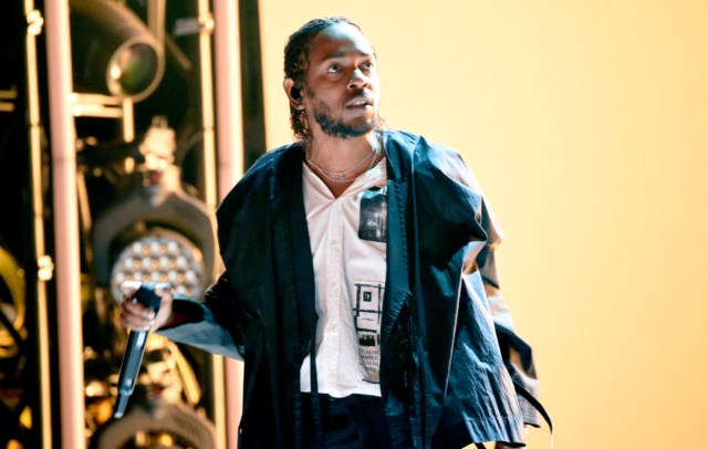 Kendrick Lamar stands with his eyes looking off-camera during a stage performance