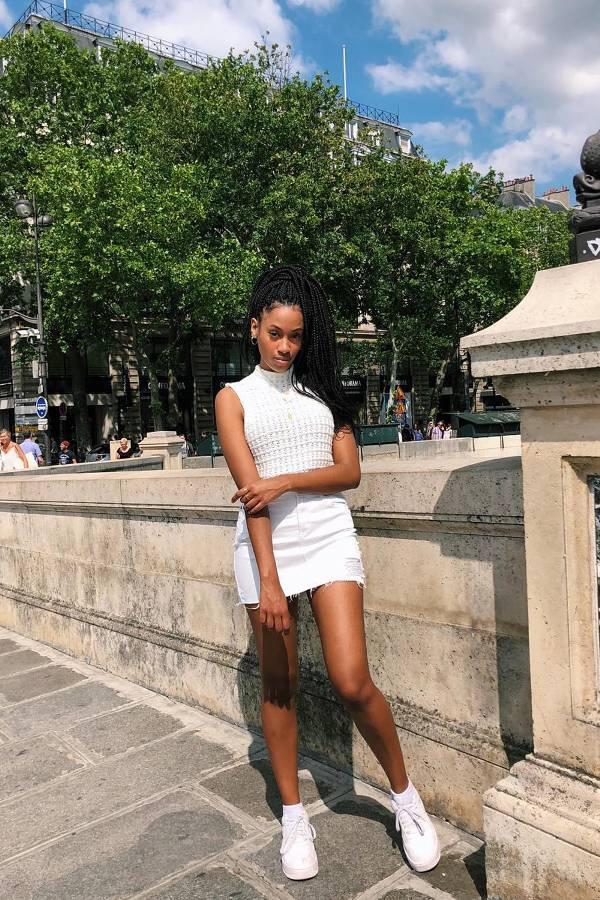 Девушка в белой мини юбке, топ и кроссовки
