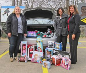 """Sheila Troyer and Kelly Troyer from Everence Financial (right) drop off gifts to Kelly Klein from Lighthouse Ministries (left) for its """"Affordable Christmas"""" project.  The annual project makes it possible for parents of at-risk children to buy gifts for their kids at significantly reduced prices."""