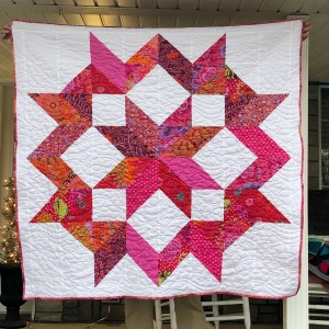 Photo of a Carpenter's Star quilt with pink and purple fabrics.
