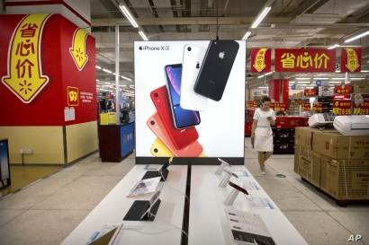 A woman uses her smartphone as she walks past a display for the Apple iPhone XR at a supermarket in Beijing, Tuesday, May 14, 2019. Sending Wall Street into a slide, China announced higher tariffs Monday on $60 billion worth of American goods.