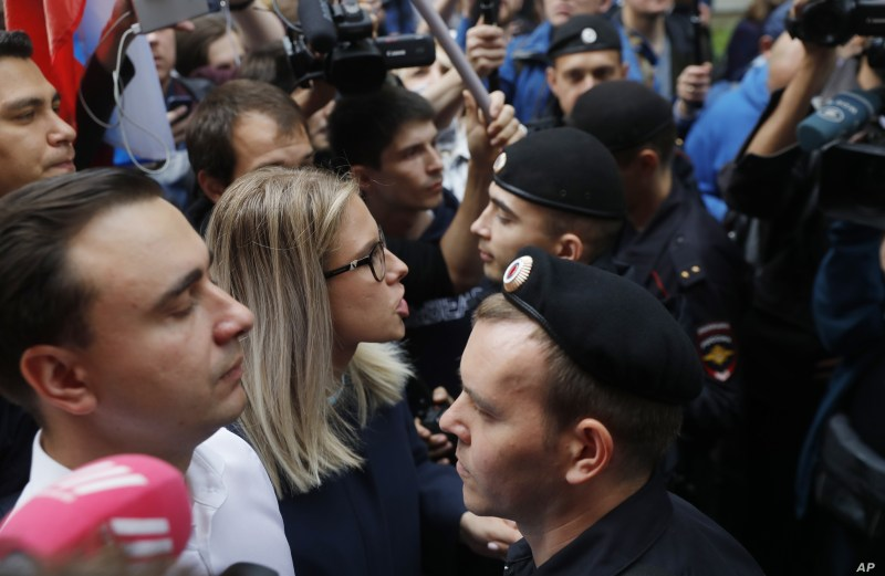 Russian opposition candidate and lawyer at the Foundation for Fighting Corruption Lyubov Sobol, center, and others stand in front of a police line during a protest in Moscow, Russia, July 14, 2019.