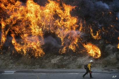 Flames from a backfire, lit by firefighters to stop the Saddleridge Fire from spreading, burn a hillside in Newhall, Calif., on…