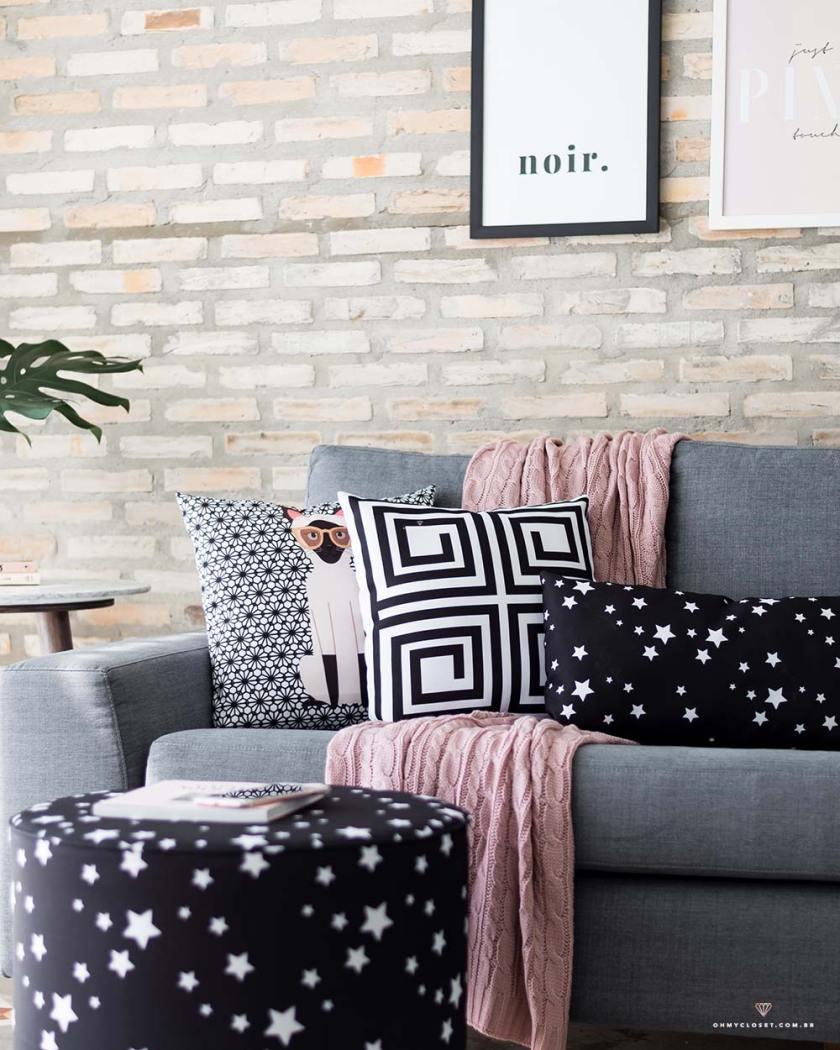 Sala de estar com sofá cinza e toque de preto e rosé. Itens de decorações da marca Nita Faco.