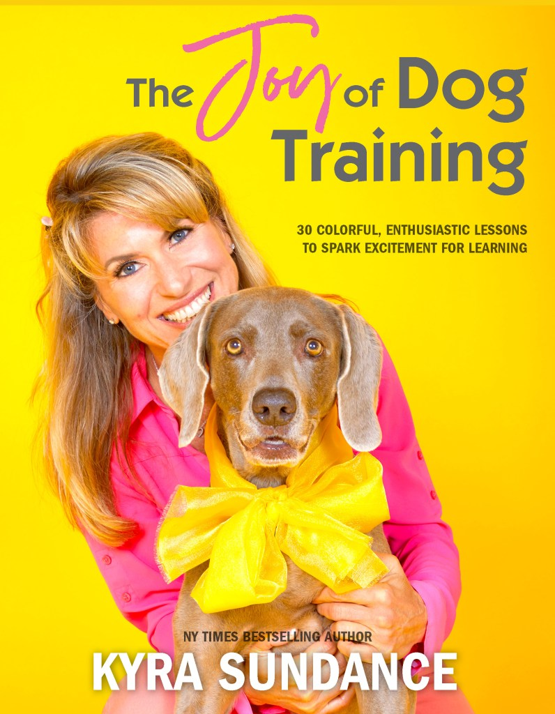 The cover of The Joy of Dog Training features the author in a hot pink blouse and her Weimaraner dog wearing a neon yellow bow.
