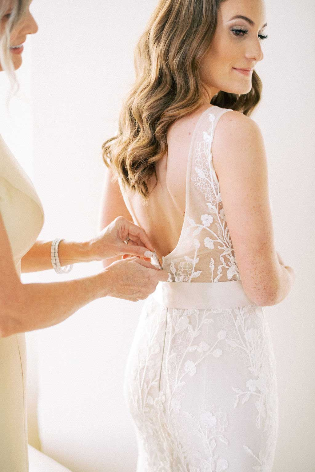 mother of the bride helps bride button her wedding dress.