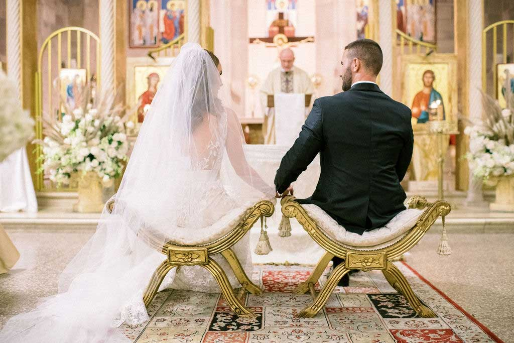 bride and groom sit on alter of church.