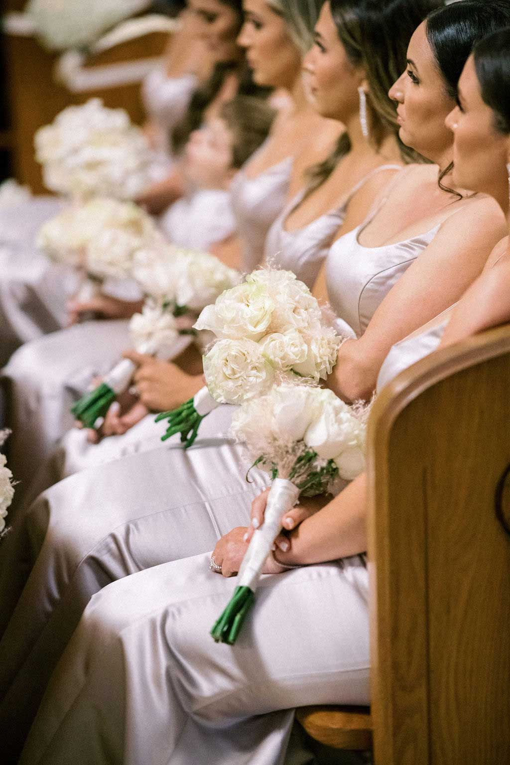 closeup of bridesmaids sitting at the pew holding their bouquets.